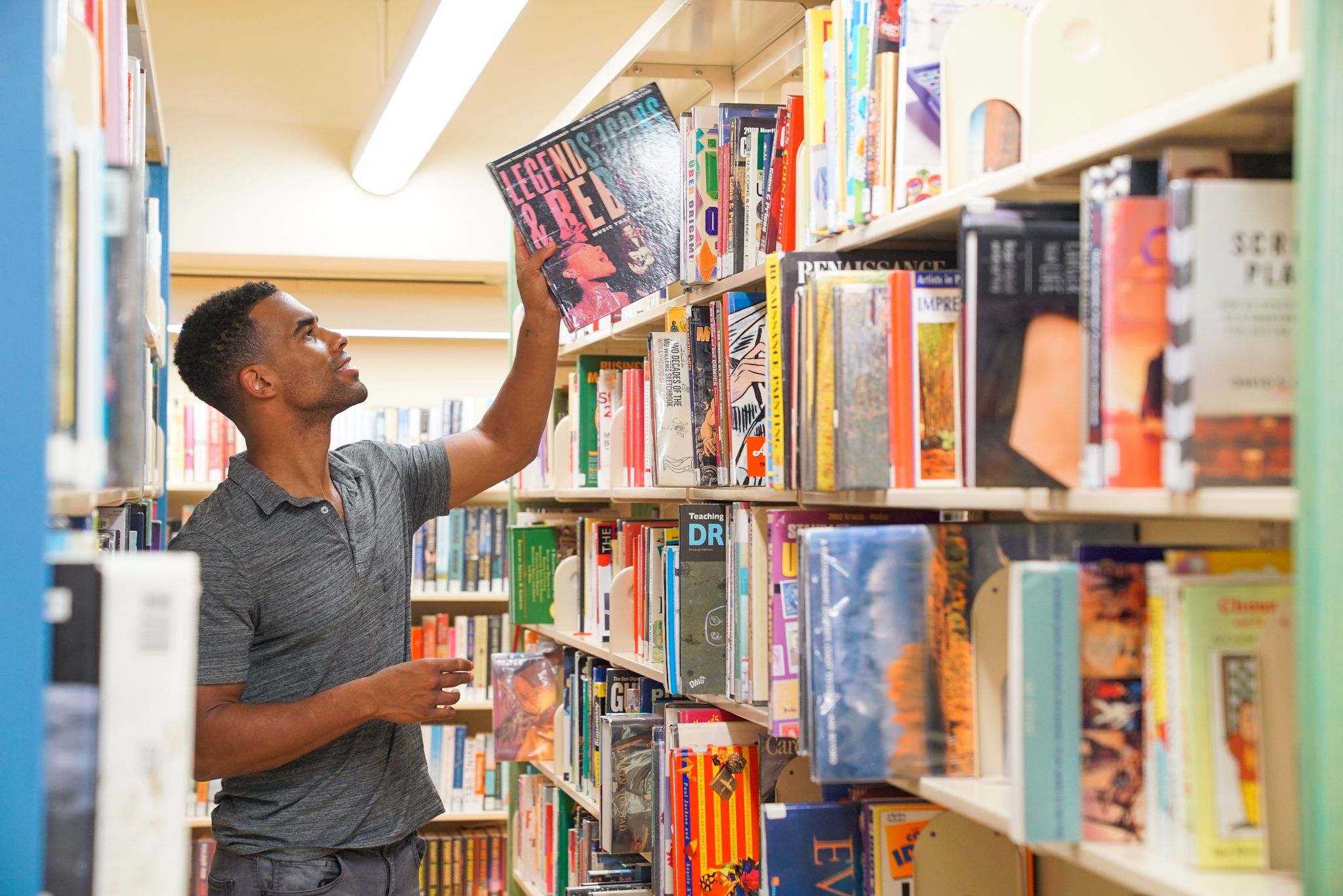 A man getting a book from the shelves of Queens Library at LeFrak City Apartments Corona
