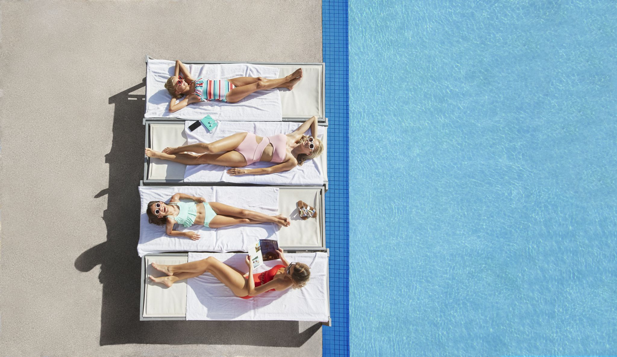 Four Women Sunbathing by the Pool at the Shoreline at Solé Mia Luxury Apartments in North Miami