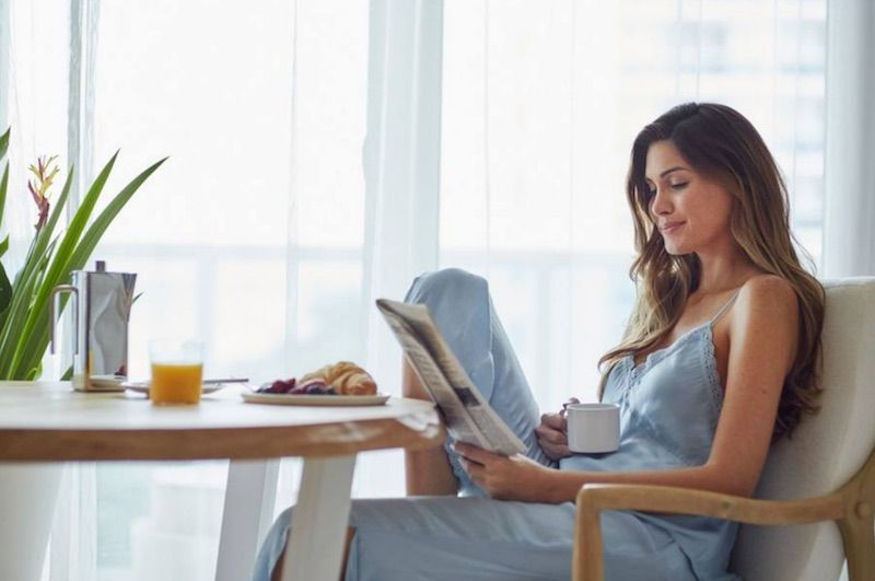 Lady Resident Drinking Coffee and Reading a Newspaper in her Luxury Apartment in North Miami, FL