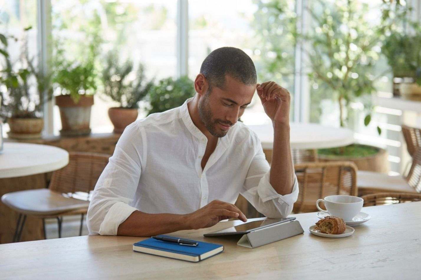 Man on His Tablet While Having Coffee at the Shoreline at Solé Mia Luxury Apartments in North Miami